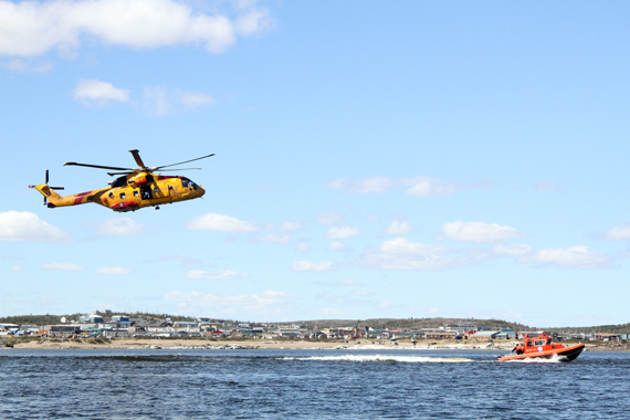 A Cormorant helicopter from Nova Scotia flies above a search vessel on Kuujjuaq's Koksoak river as part of a 2014 simulated rescue scenario. Kuujjuaq officials hosted the Northern SAR Roundtable met in the Nunavik community last week. (PHOTO COURTESY OF THE KRG)