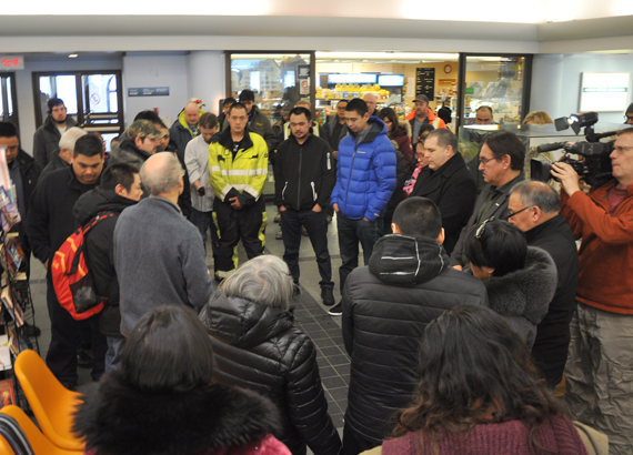 Rev. Mike Gardener leads F/V Saputi crew members in a seafarer's prayer upon their return to the Iqaluit airport Feb. 26. (PHOTO BY SARAH ROGERS)