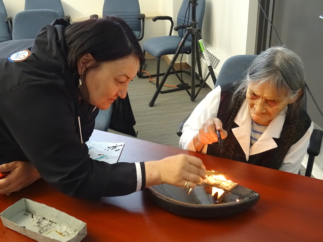 NTI President Cathy Towtongie helps an elder light the qulliq in September 2015. Towtongie says the revised Nunavummi Nangminiqaqtunik Ikajuuti policy has been submitted to the Government of Nunavut for approval. (FILE PHOTO)