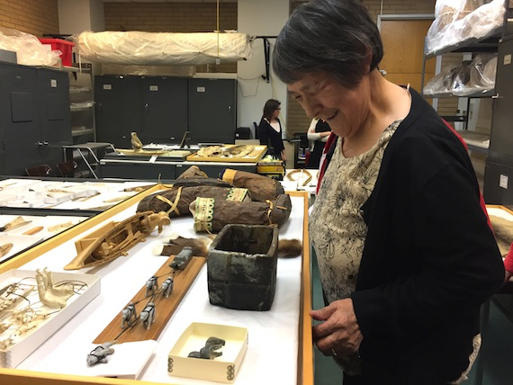 Mary Avalak examines Inuit artifacts from the Doug Lord collection at the University of Alberta. (PHOTO BY PAMELA GROSS)