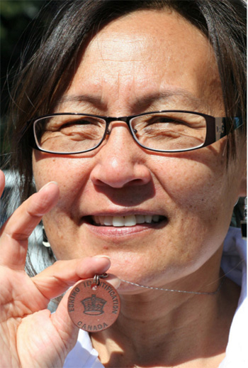 Leena Alivatuk, one of the Ottawa-based Inuit features in Pottle's photo series, wears her identification disc on a necklace. (PHOTO COURTESY OF B. POTTLE/FEHELEY FINE ARTS)