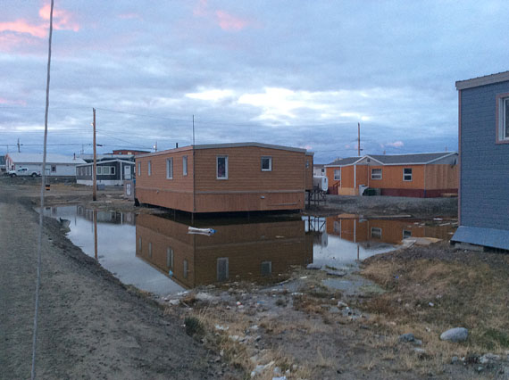 This five-bedroom house in Rankin Inlet, now completely surrounded by water, is home to an 80-year-old elder and five families, including seven children aged nine months to 12 year old.  Every spring, meltwater collects underneath and surrounding the home, creating mold and other safety issues. (PHOTO BY MARY-ROSE ANGOSHADLUK)