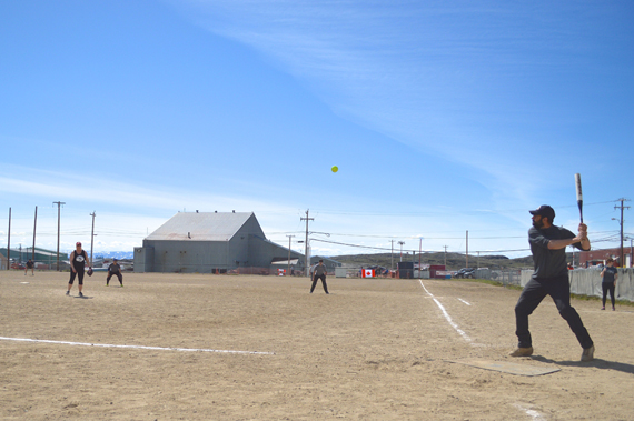 Warm weather and clear skies grace the first two days of Iqaluit's annual Canada Day-weekend softball tournament, with temperatures reaching into the double-digits. Clouds and cold winds moved in on the final day of the tournament July 3 and had many players retreating under blankets in the dugout when they weren't on the field. Team NASLs & Pitches went the distance after a long day of playoff rounds, beating out eight other teams to win the tournament and hoist the coveted Canada Day Cup trophy. (PHOTO BY STEVE DUCHARME)