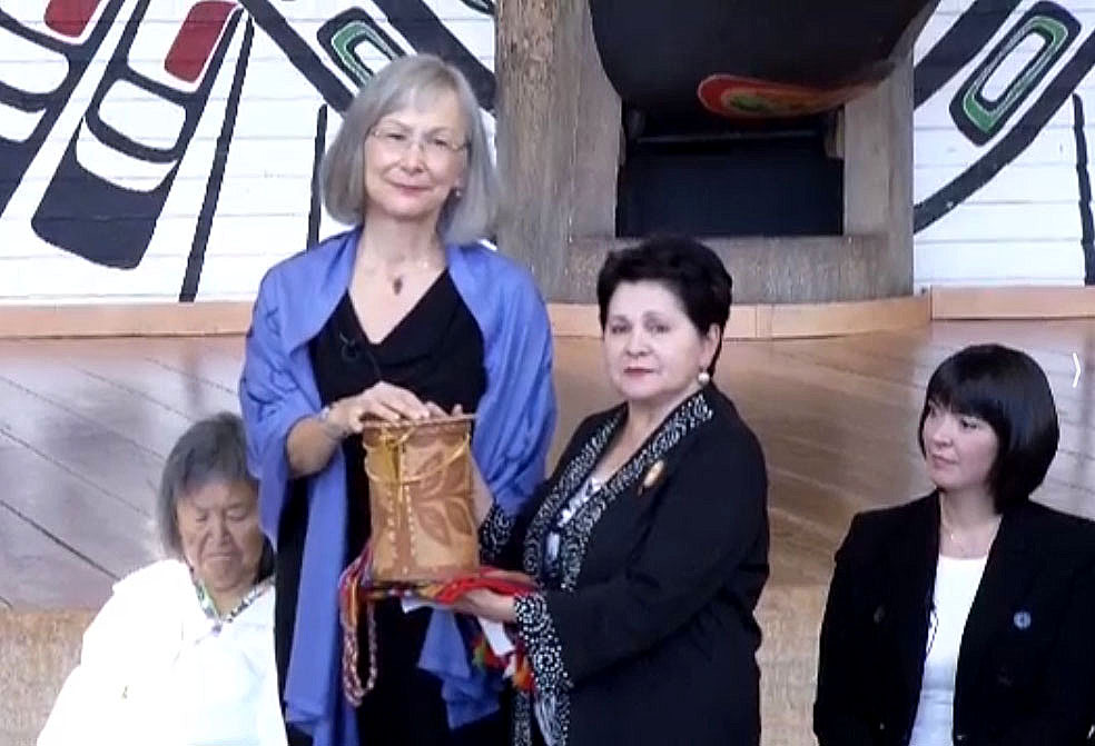 Marion Buller, a First Nations judge who sits on the B.C. provincial court (standing) who will serve as chief commissioner of the federal government's National Inquiry into Missing and Murdered Indigenous Woman, receives a gift from an Algonquin elder at the inquiry's Aug. 3 launch in Gatineau, Que. On the left is Inuit elder Sally Webster and on the right sits Qajaq Robinson, one of the other four commissioners. The first phase of the inquiry will cost nearly $54 million and run from Sept. 1, 2016 until Dec. 31, 2018. At the same time, Justice Canada will give provinces and territories $11.67 million over three years to fund family liaison services and another $4.5 million for victims services. Read more on Nunatsiaqonline.ca (VIDEO CAPTURE)