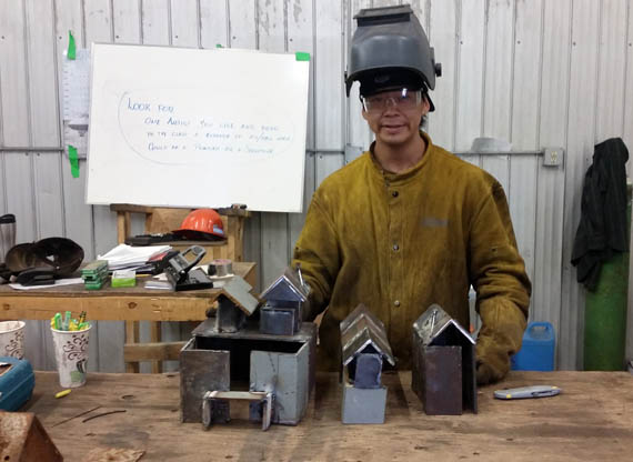 Ian Alikaswa shows off the tiny houses and buildings that make up his metal village Aug. 30 in Arviat, as part of the hamlet's artistic welding workshop, which runs until Sept. 1. (PHOTO COURTESY OF M, MALLA)