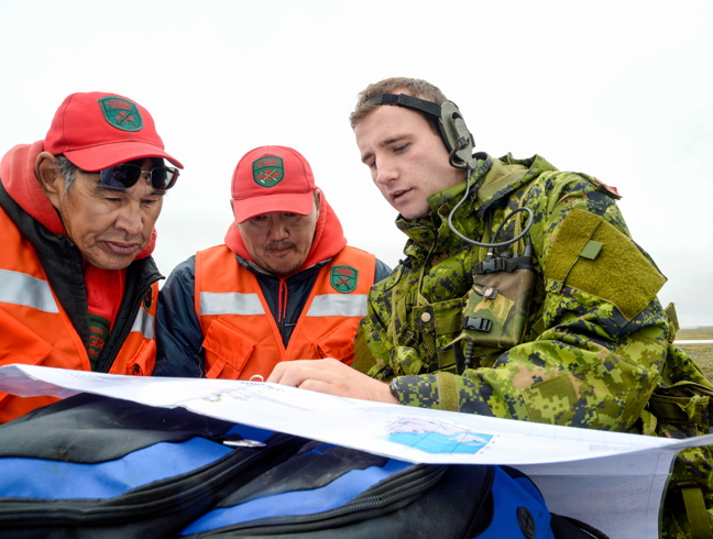 Captain Matthew Szostk, right, from The Royal Montreal Regiment, discusses route options with members of 1 Canadian Rangers Patrol Group, Master Corporal Andy Aliyak, left, and Ranger John Ussak, centre near Rankin Inlet Aug. 21. The soldiers and rangers are in Rankin Inlet for this year's Operation Nanook, an annual northern training exercise to teach soldiers, as well as air and navy personnel, how to operate in Canada's northern terrain and climate. This year's exercise involved simulated ground combat exercises near Rankin Inleet and also potentially north of Chesterfield Inlet. (PHOTO BY BELINDA GROVES)