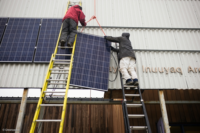 A Vancouver Renewable Energy Co-op solar installer, Duncan Martin, left, and the Greenpeace logistics coordinator, Claude Beauséjour, install solar panels on the Clyde River community hall this past August. (GREENPEACE PHOTO)