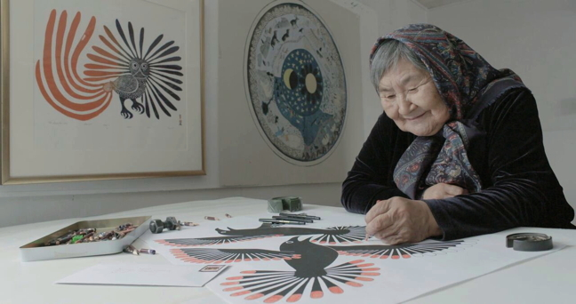 A still from the new Heritage Minute showing artist Kenojuak Ashevak working on a bird print of which she was renowned. On the wall to her right are two famous images of Ashevak's: Enchanted Owl and Nunavut Qajanartuk/Our Beautiful Land, commissioned by then-Indian Affairs and Northern Development to commemorate the signing of the Nunavut Land Claim Agreement-in-Principle in 1990. That image eventually graced the cover of the final agreement. (HERITAGE MINUTE STILL)