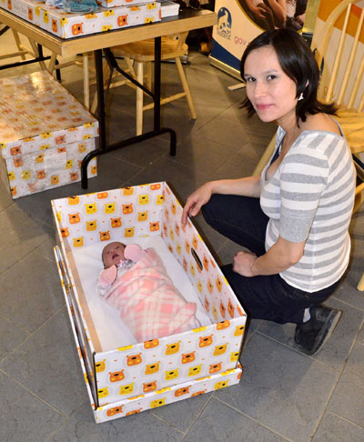 Emily Shoapik of Pangnirtung places her two-week-old newborn Rachel Shoapik into one of the Finnish-style baby boxes that the Government of Nunavut's Department of Health will distribute to the parents of newborn infants over the next year. (PHOTO BY JIM BELL)