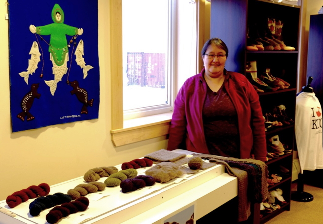 Nancy Kadlun, works at the Kugluktuk Visitor's Centre, stands beside some Qiviut Project products. (PHOTO COURTESY QIVIUT PROJECT)