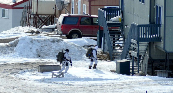 Armed police in white winter camouflage outfits search around houses in Iqaluit's Happy Valley neighbourhood, which was locked down for 41 hours between April 28 and April 30, 2015. Jamie Mikijuk, now 28, will serve another 372 days in jail after pleading guilty to a firearms charge. (PHOTO BY THOMAS ROHNER)