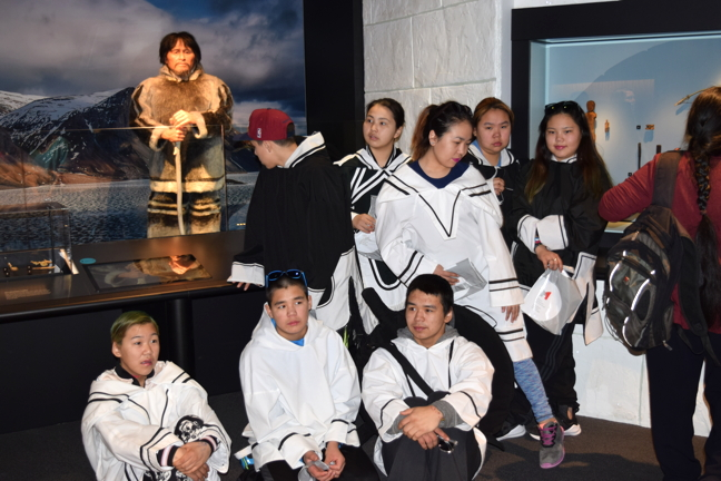 Students from Arctic Bay, and other Nunavummiut, stand near Nuvumiutaq, a remarkably real looking replica of a Thule man from the Arctic Bay area. Museum staff invited their Inuit guests for a sneak peak of the replica in advance of the public unveiling this July.