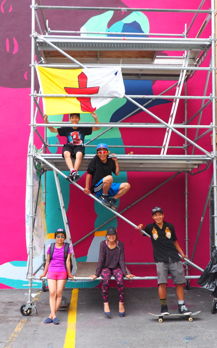 Embassy of Imagination artists from Cape Dorset pose on the scaffolding in front of the huge mural they just painted and unveiled in Ottawa's Byward Market July 16. The artists include Harry Josephee, Kevin Qimirpik, Janice Qimirpik, Christine Adamie and mentor Parr Josephee. (PHOTO BY COURTNEY EDGAR)