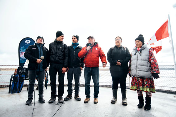 C3 expedition leader Geoff Green speaks during a live broadcast for an underwater Arctic dive led by the ocean education group the Fish Eye Project. Divers and ocean scientists involved are standing to his left, and the Cambridge Bay representative for Ocean Networks Canada Mia Otokiak is to his right, along with Cambridge Bay elder Eva Kakolak. (PHOTO COURTESY OF CANADA C3)