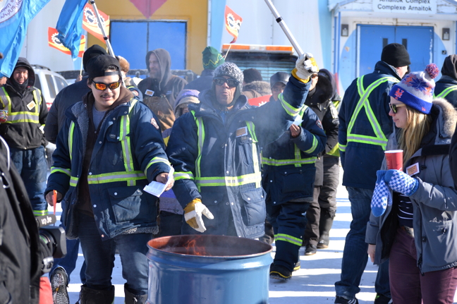 About 50 City of Iqaluit employees took turns throwing copies of a wage-freeze letter they got from their employer into a burning oil drum, March 30, in front of city hall. (FILE PHOTO)