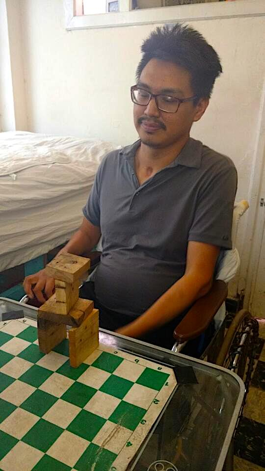 Napu Boychuk eyes the tower he was recently able to build, by himself, with wooden blocks, a huge achievement because, until recently, he had no use of his arms. (PHOTO COURTESY OF T. BOYCHUK)