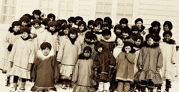 Inuit children from the western Arctic gather outside a residential school in this undated file photo. MPs passed a motion May 1 asking the Pope to issue an apology on behalf of the Canadian Catholic church for its role in operating dozens of residential schools over the last century. (FLEMMING/NWT ARCHIVES: N-1979-050-0101)