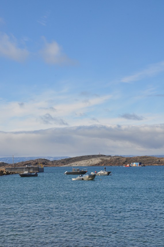 Open-water season is in full swing across much of Nunavut. Boats line the breakwater in Iqaluit, as a barge in the background ferries sealift cargo onto the mainland. (PHOTO BY SARAH ROGERS)