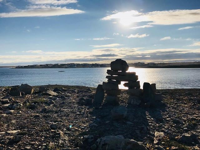 Brennan Ehaloak snapped this shot of an inuksuk standing in front of Cambridge Bay's old stone church, with the Kitikmeot community visible in the background across the bay. (PHOTO BY B. EHALOAK)