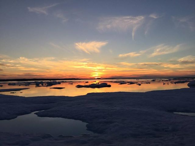 Angele Urajak Arragutainaq watches the sun go down outside of Sanikiluaq July 23. The Belcher Island community is enjoying sunny, cloudless skies this week, with Environment Canada forecasting little wind and temperatures hovering around 15 C. (PHOTO BY A. ARRAGUTAINAQ)