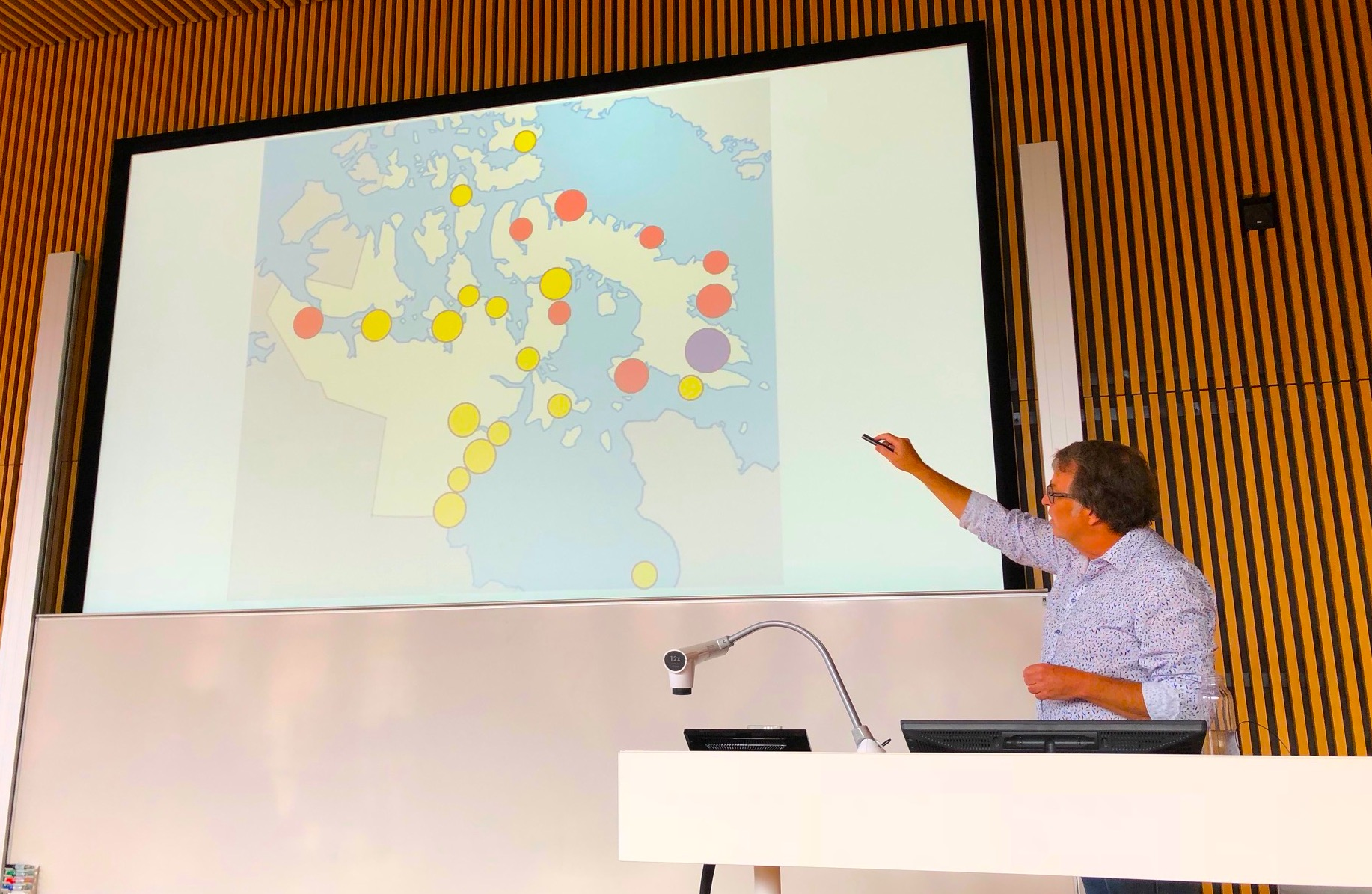 Researcher Jack Hicks points at a map of Nunavut where red dots show the communities where suicides have been more numerous. Hicks presented a new suicide prevention project at the International Congress of Circumpolar Health on Aug. 14 in Copenhagen. (PHOTO BY JANE GEORGE)
