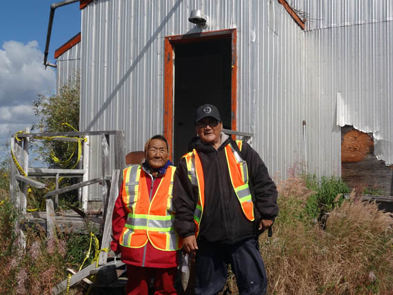 Elder Mary Anowtalik, the only surviving Ahiarmiut who can recall the relocations from Ennadai Lake, stands in from of the weather station there with her son Paul E. Anowtalik in August 2013. Ahiarmiut hope to see a memorial eventually set up on the site. (FILE PHOTO)