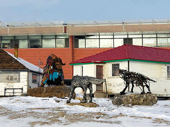 A muskox is circled by two wolves—at least, that's the scene being portrayed by these scrap-metal sculptures that stand in front of Cambridge Bay's heritage park. In the background, you can see the community's new town hall. (PHOTO BY JANE GEORGE)