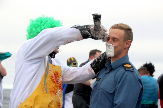 Neptune's barber gives a clean shave to the sailors of HMCS Charlottetown during a ceremony held for the ship's crossing of the Arctic Circle. (PHOTO BY BETH BROWN)