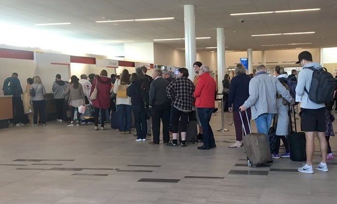 After a night spent in Iqaluit, the passengers who arrived in Nunavut during the evening of Wednesday, Sept. 12, on British Airways Flight 103 line up at 11 a.m. the following morning to board the replacement aircraft that will take them to their destination. (PHOTO BY FRANK REARDON)