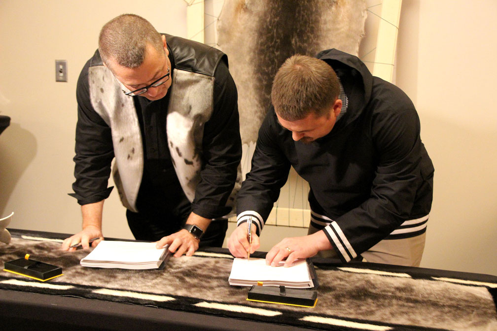 P.J. Akeeagok (right,) president of the Qikiqtani Inuit Association, and Brian Penney, president and CEO of Baffinland Iron Mines Corp. sign an amended Inuit impact benefit agreement Oct. 3 in Iqaluit. (PHOTO BY BETH BROWN)