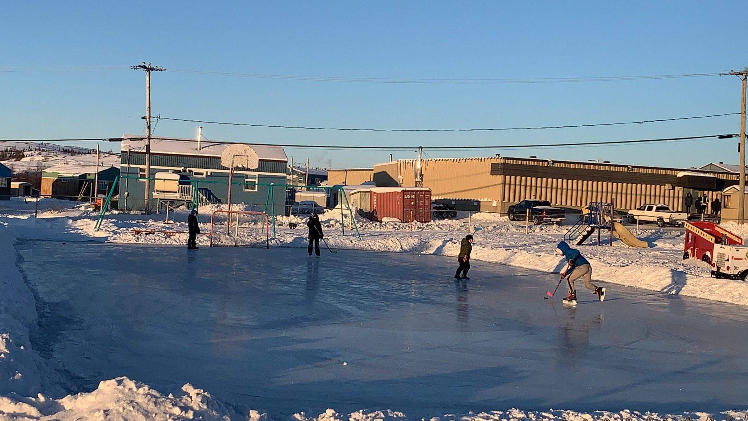 Children in Kuujjuaq play hockey at an outdoor rink in the middle of town on Dec. 9. (Photo by Malaya Qaunirq Chapman)