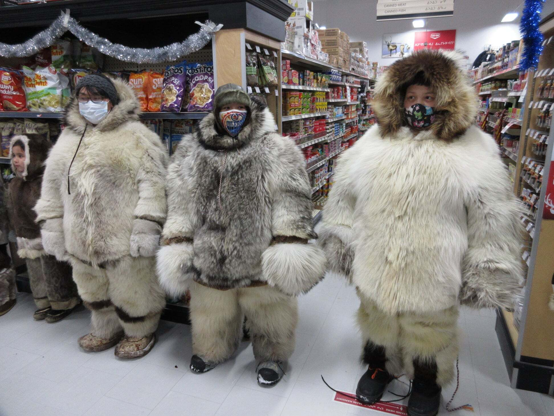 Naujaat residents decked themselves out in clothing made from polar bear, seal, caribou and fox Dec. 21 to participate in their co-op store's annual traditional clothing contest. (Photo courtesy of the Naujaat Co-op)