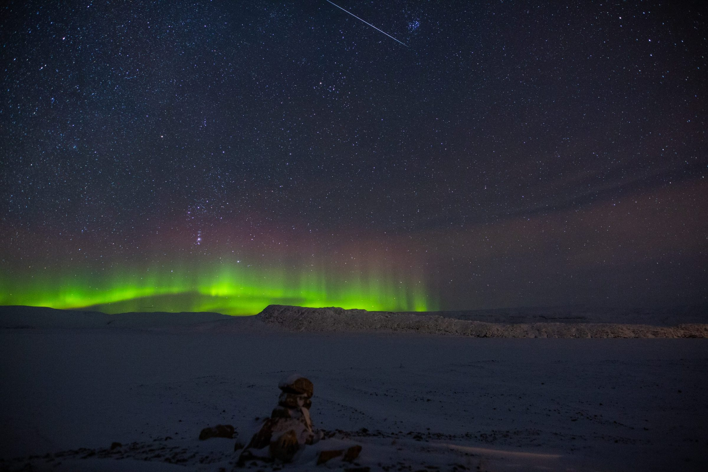 """An Orionid meteor streaks through the night sky above Arctic Bay around 1 a.m. on Dec. 14 in this image taken by Clare Kines. """"It's taken overlooking Marcil Lake and shows an Orionid meteor near the constellation Pleiades,"""" he writes. """"Orion is visible in the photo as well as some aurora to the south of us."""" (Photo by Clare Kines)"""