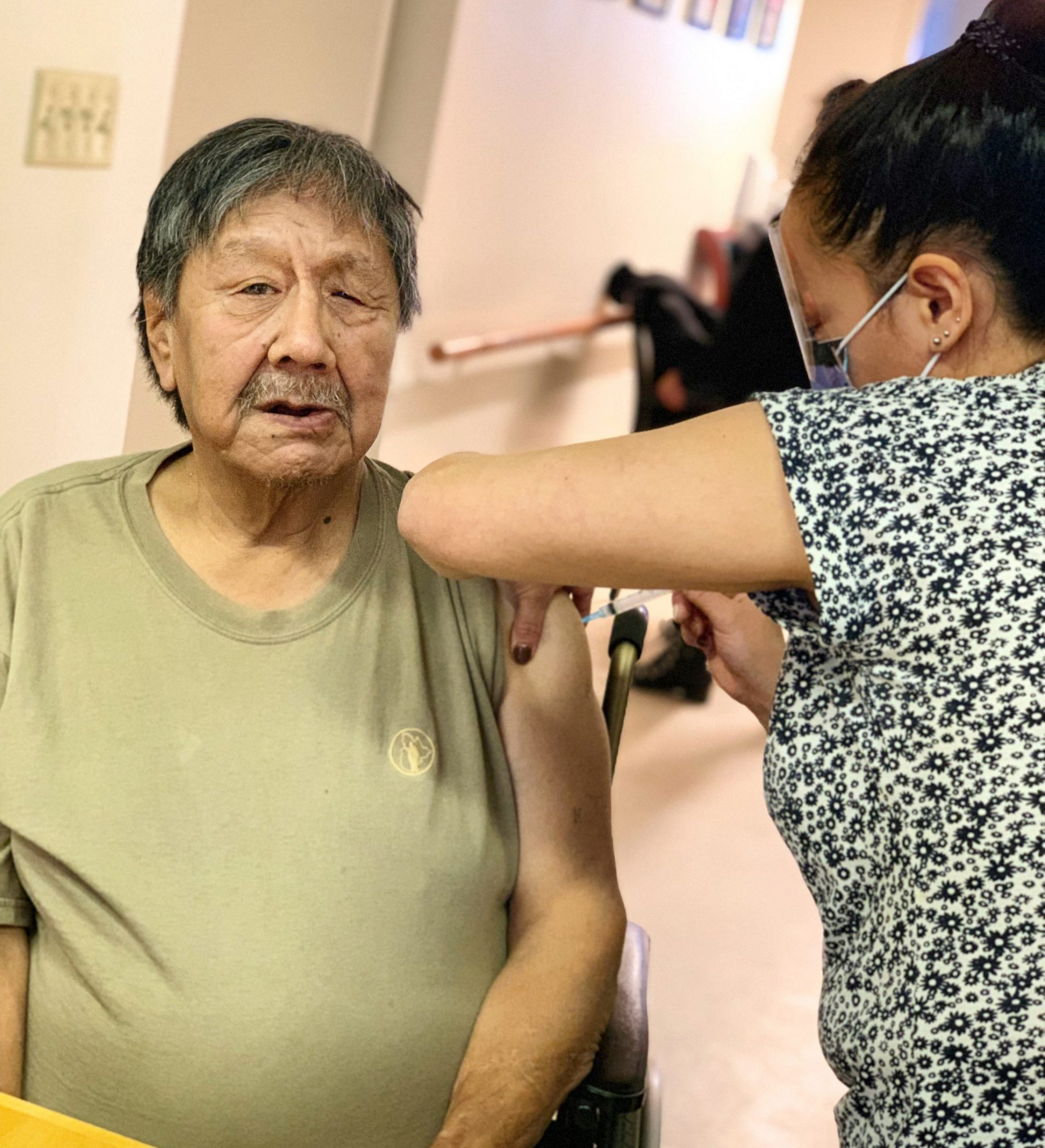 Josephee Adams, 70, is Nunavut's first recipient of a COVID-19 vaccine. Adams, a resident of the Iqaluit Elders' Centre, received the vaccine today from public health nurse Susie Pearce. (Image courtesy of the Government of Nunavut)