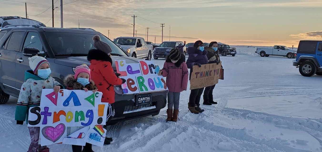 """Arviat residents gather on Friday, Jan. 8, to host a send-off parade for Dr. Carl Leroux, the doctor who works out of the community health centre, before he headed home to B.C. the same day. Typically, as part of his rotation, Dr. Leroux spends four to six weeks in Arviat at a time. When he last arrived in October, Dr. Leroux treated the first cases of COVID-19 in Arviat and decided to stay in the Kivalliq community through the outbreak, until the case count was back to zero. """"We are very grateful that he decided to stay and help the medical team here in Arviat during the COVID-19 outbreak, which showed us he does care for the people of Arviat,"""" said Nataasha Hilu Komakjuak. (Photo courtesy of Nataasha Komakjuak)"""
