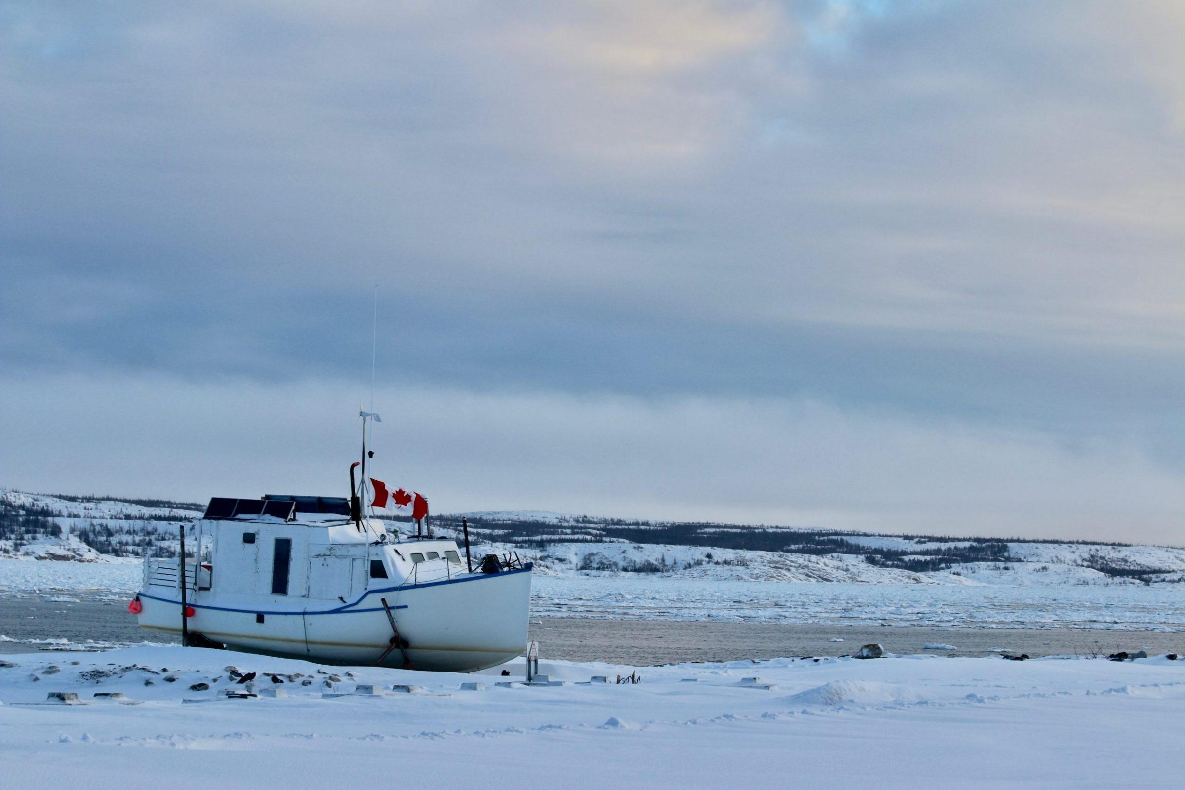 "A boat sits on the banks of the Koksoak River near Kuujjuaq Jan. 18. ""Super late into the season, and still, the Kuujjuaq River isn't frozen,"" writes Malaya Qaunirq Chapman. (Photo by Malaya Qaunirq Chapman)"