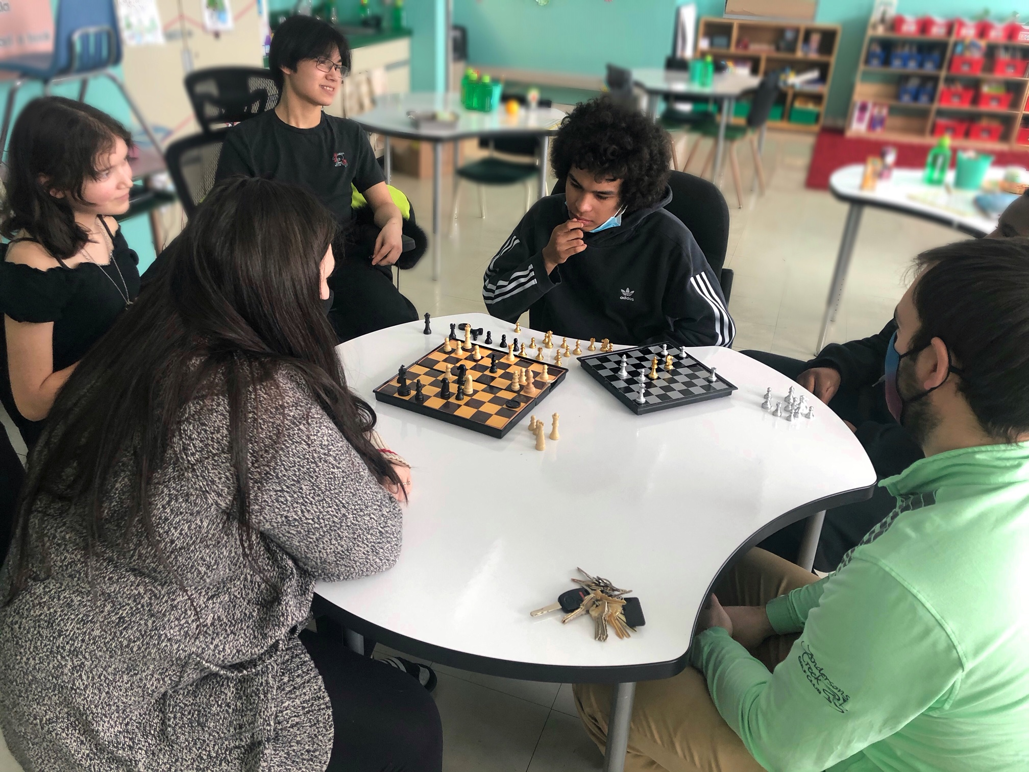 Matthew Hubloo, a Secondary 2 student at Jaanimmarik School here in Kuujjuaq, plays two chess matches simultaneously against the school's vice-principal, Nicholas Ramsay, and Grade 4 English teacher, Sarah Nickerson, on Jan. 26. Hubloo won both games. (Students at the school are not required to wear masks in the classroom.) (Photo by Isabelle Dubois)