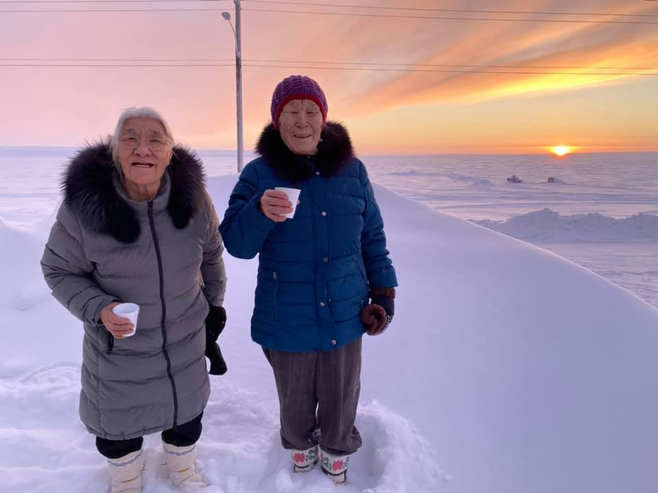 """Cambridge Bay elders Bessie Pihuak Omilgoetok, left, and Mary Akariuk Kaotalok, who are both in their 80s, celebrate the return of the sun by following the same tradition that Omilgoetok learned from her grandparents, on Wednesday, Jan 13. """"The practice is to have a drink of water to welcome and honour the sun so it always comes back and then throw the water towards the sun for it to return again,"""" the Pitquhirnikkut Ilihautiniq, or Kitikmeot Heritage Society, said in a social media post. """"We do this in honour of our ancestors, traditions, culture and language. We will do this every year to keep this tradition going in celebration of who we are as a people: Inuinnaujugut."""" (Image courtesy of Pitquhirnikkut Ilihautiniq / Kitikmeot Heritage Society)"""