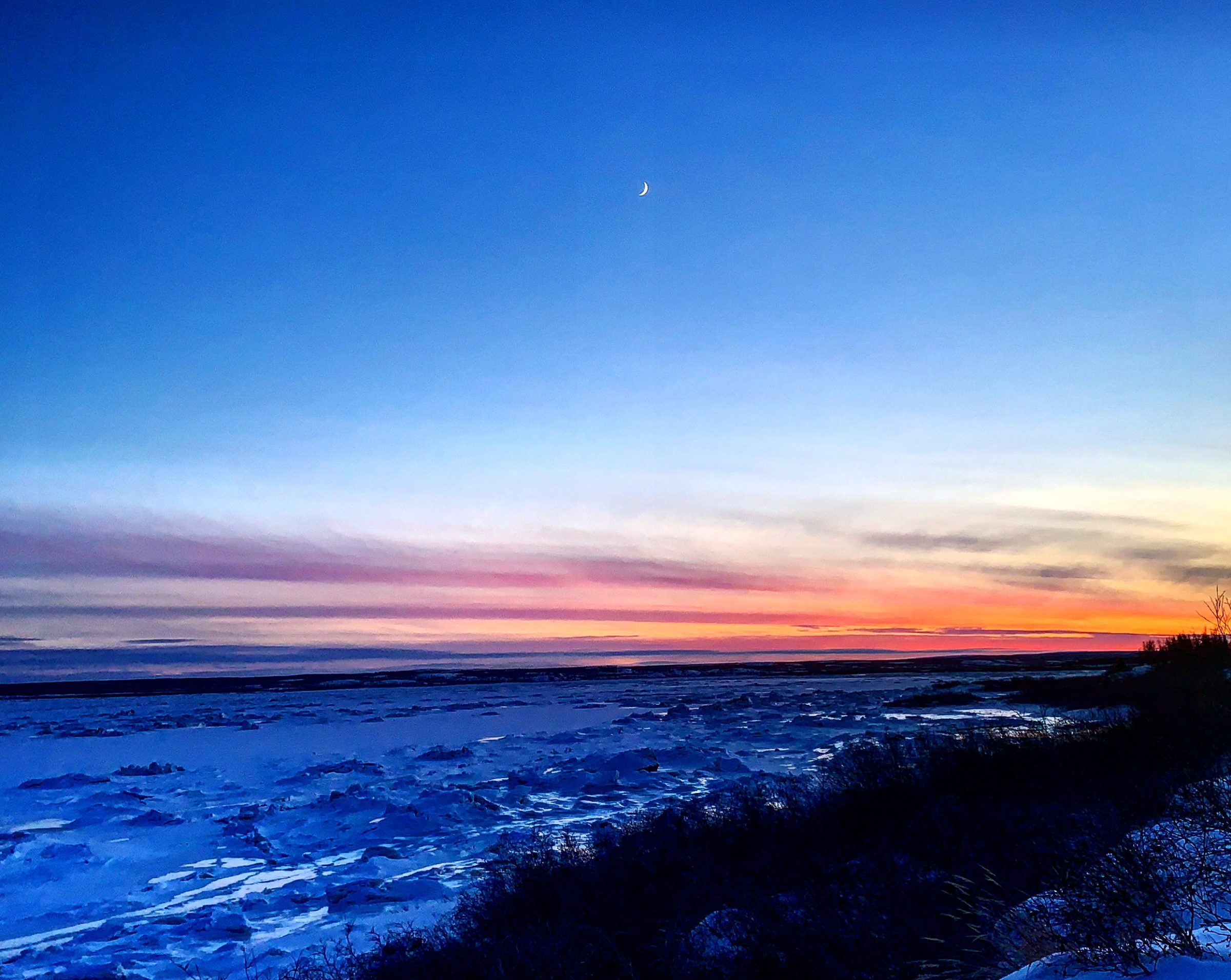 """A waxing crescent moon hangs in the sky above the Koksoak River near Kuujjuaq, as seen from the Range neighbourhood on the afternoon of Jan. 16. """"Further out in the middle of the river, there's still a huge strong river flowing,"""" writes Malaya Qaunirq Chapman. """"This warm weather is wild for January."""" (Photo by Malaya Qaunirq Chapman)"""