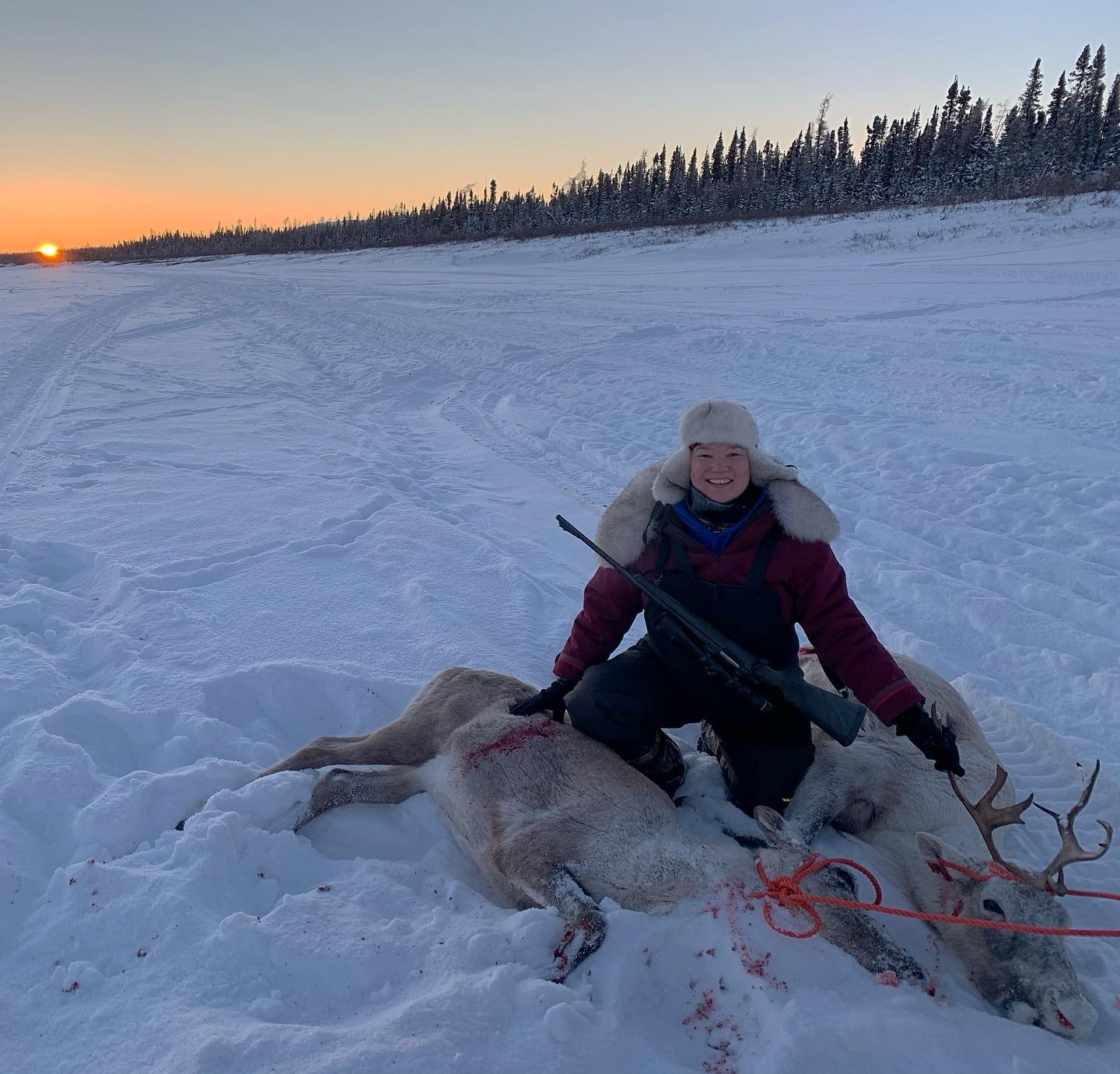"Malaya Qaunirq Chapman poses next to two caribou she caught, 190 kilometres up river from Kuujjuaq on Jan. 31. ""I'm so happy to do as my ancestors did, hunt long distances and provide for my friends and family. I'm in my element here,"" she writes. (Photo courtesy of  Malaya Qaunirq Chapman)"
