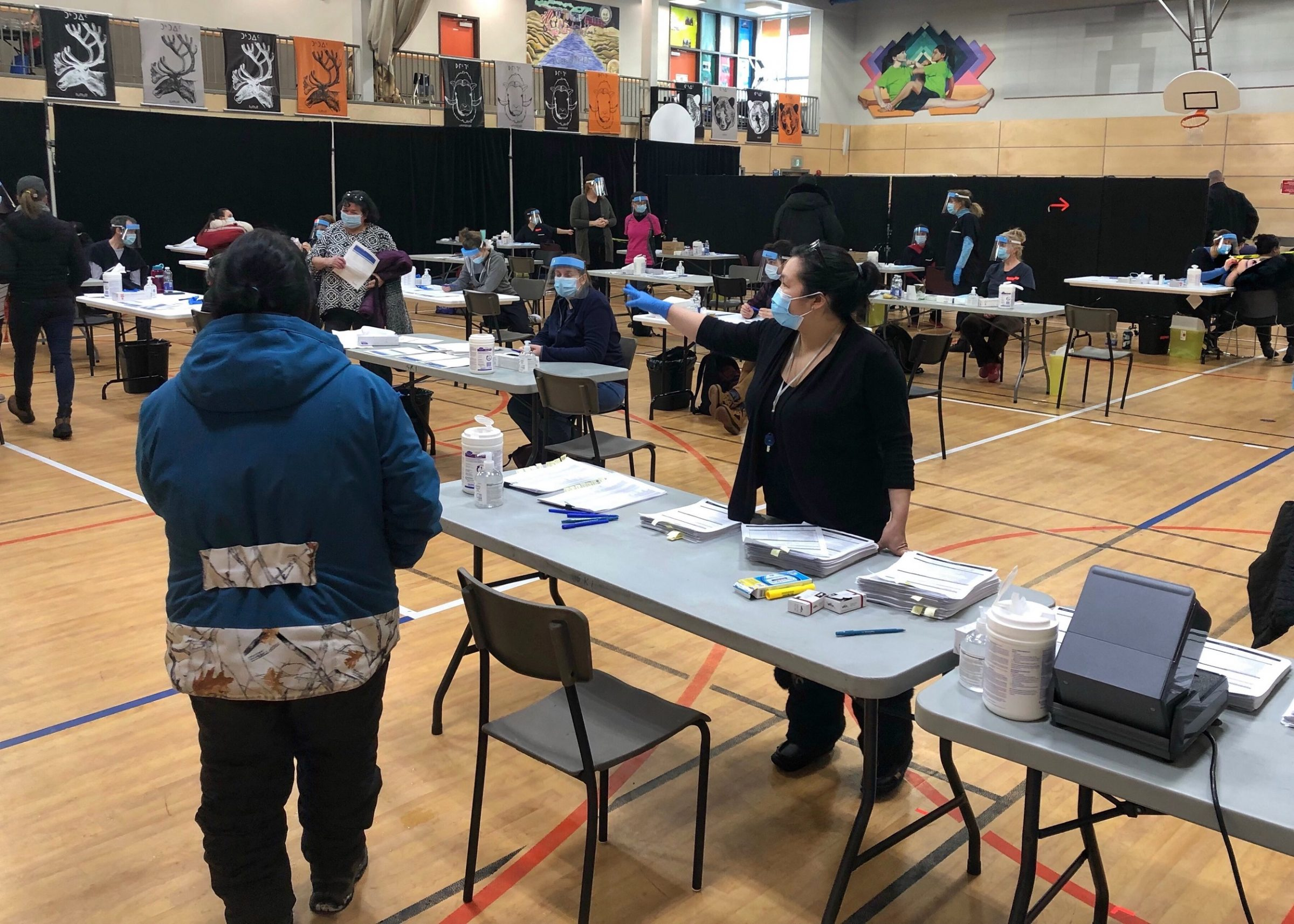 Health-care workers welcome Kuujjuaq residents to the community's first general vaccination clinic in February. Regional health authorities are now rolling out a second round of immunization clinics. (Photo by Isabelle Dubois)