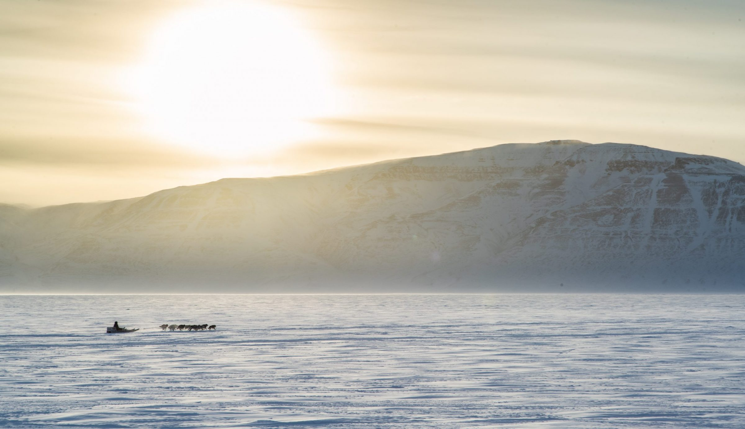 A dogsled team heads out onto Adams Sound near Arctic Bay on Feb. 20, as the sun peeks over the mountain known as Tununirusiq. (Photo by Clare Kines)