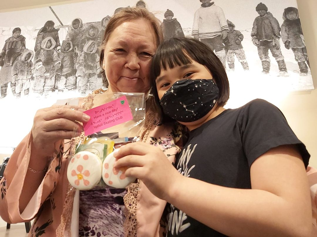 Eight-year-old Béatrice Allerton of Iqaluit delivers a gift bag of cookies and tea to Natsiq Kango, an elder originally from Arctic Bay. Allerton delivered more than 60 gift bags to Iqaluit elders on March 28 and 29 for a community service project that's part of the Iqaluit Skating Club's off-ice training, funded by Sport Nunavut. Twelve skaters and some of the club's board members prepared the gift bags with the help of baker Craig Borden. Allerton received a $500 micro-grant from Northern Youth Abroad for the project. (Photo by Laura Thompson)