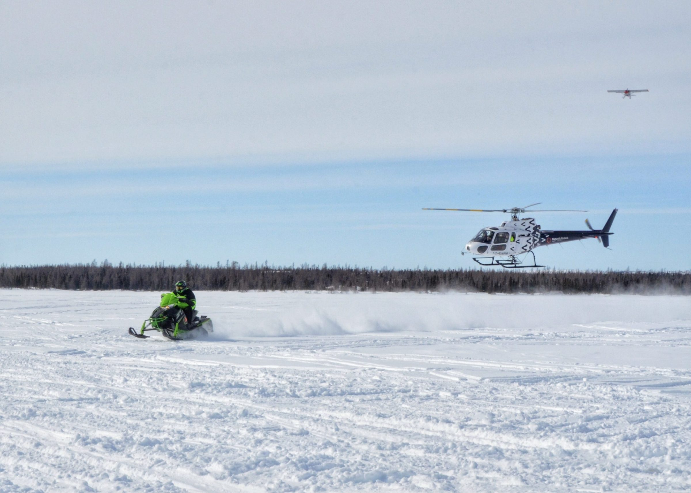 George Kauki is the winner of the men's division of Kuujjuaq's annual Easter Cross-Country Snowmobile Race held on Monday. He's seen here approaching the finish line at Tasialuk (Stewart Lake), after racing to Tasiujaq and back, covering just over 250 km. He's followed by a Nunavik Rotors helicopter, which patrolled the trail for safety during the race, with a nurse onboard in case of emergencies. (Photo by Isabelle Dubois)