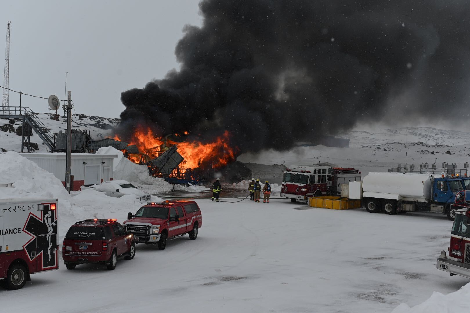 Iqaluit firefighters respond to a fire south of the airport Monday afternoon. At least three fire trucks and an ambulance were at the scene at approximately 4 p.m., as flames engulfed a building near the sewage lagoon. (Photo by Dustin Patar)