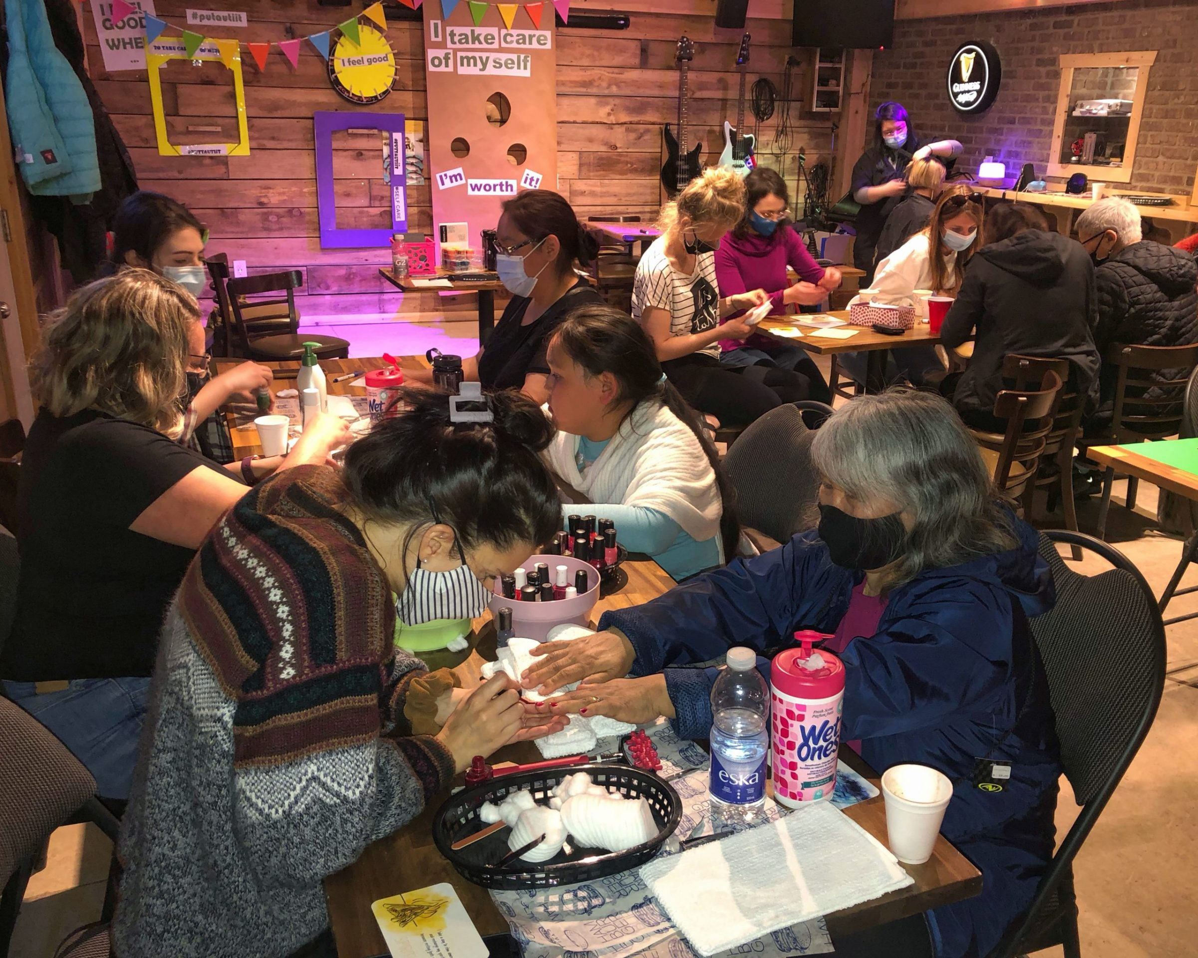 Kuujjuaq residents receive free manicures on Friday, as part of the Ungava Wellness Program's Puttautiit month-long mental health activities and workshops. The event, held at Nuna Golf, also offered massages, beading, haircuts and a funny photo booth, along with coffee, tea, smoothies and healthy snacks. (Photo by Isabelle Dubois)
