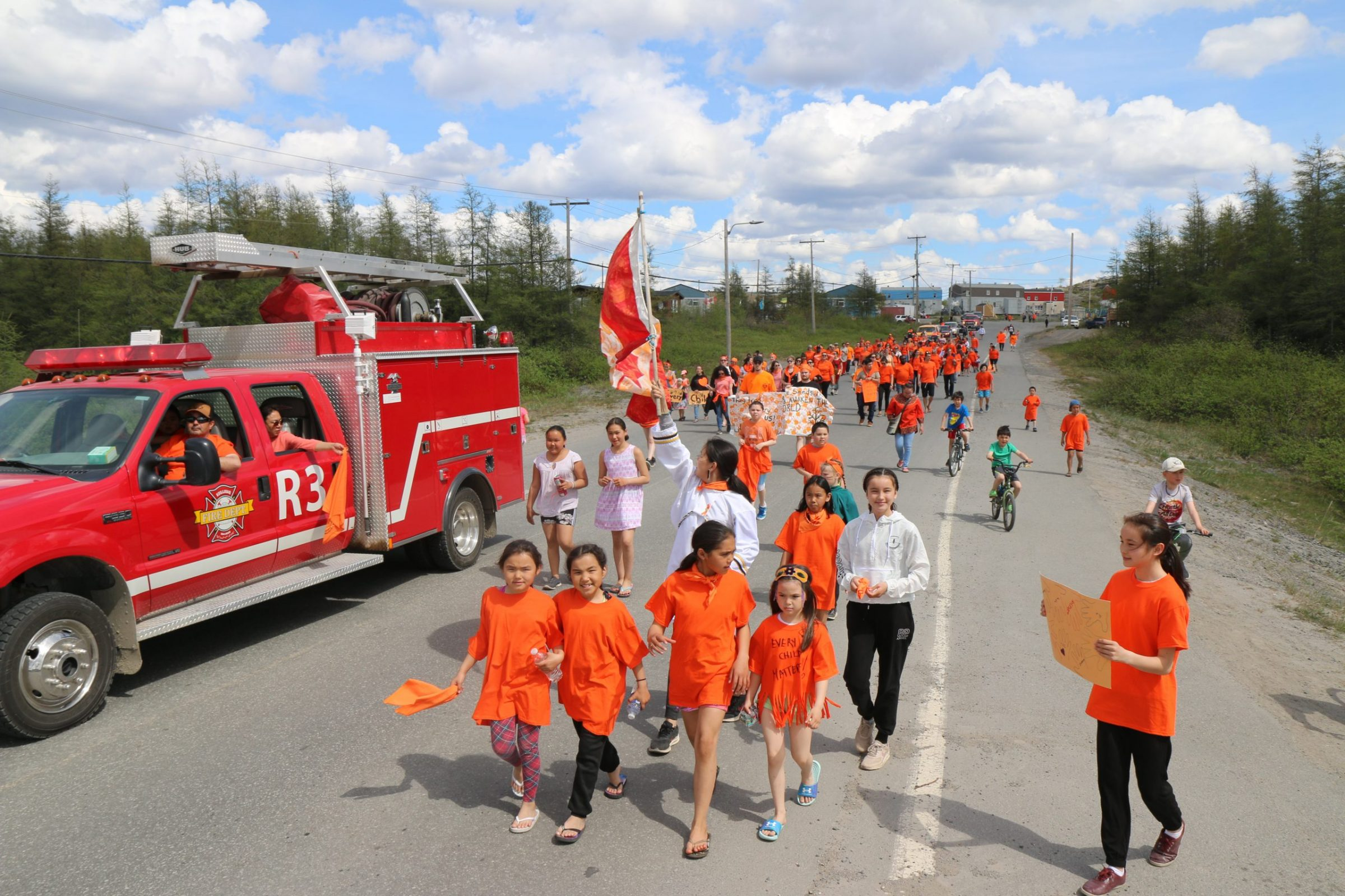 """More than 100 Kuujjuaq residents attended a parade on National Indigenous Peoples Day on Monday to honour children lost to Canada's residential school system, following the recent discovery of the remains of 215 children at a former residential school in Kamloops, B.C. Many attendees wore orange, a colour associated with the Every Child Matters campaign, which honours the experience of residential school survivors. """"I'm so happy to see so much orange to show support of this initiative,"""" said organizer Lavinia Flaherty. (Photo by Malaya Qaunirq Chapman)"""