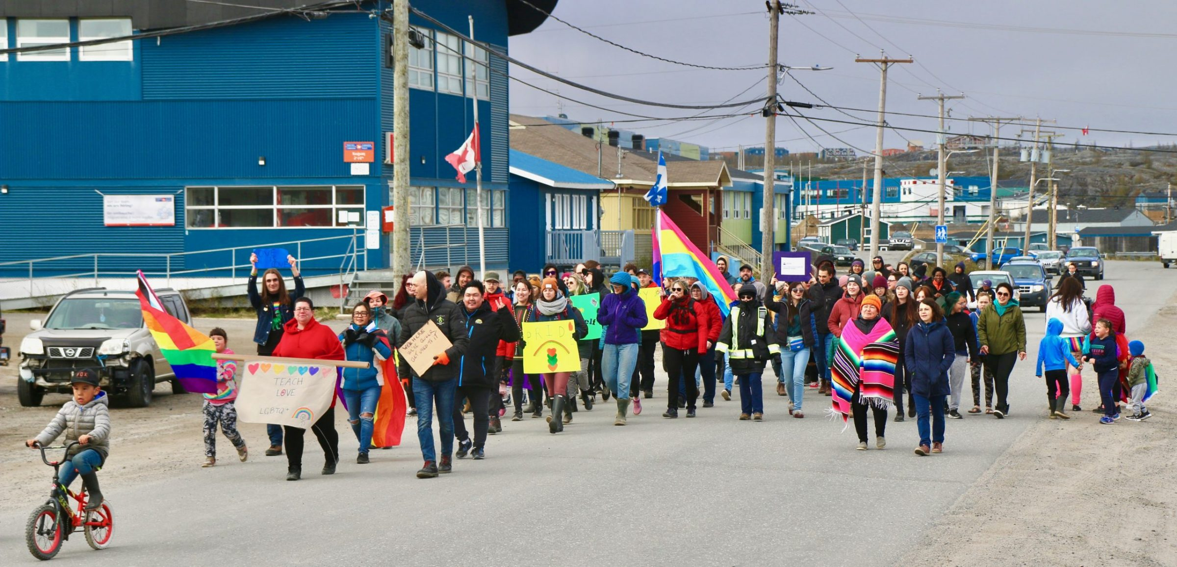 """Kuujjuaq residents participate in what organizers say is the community's first pride parade on Wednesday. About 80 people attended to show support for LGBTQ+ in the community. """"The group had lots of positive feedback and everyone was excited and glad that Kuujjuaq had its first pride parade,"""" said organizer Aputi Unatweenuk. (Photo by Malaya Qaunirq Chapman)"""