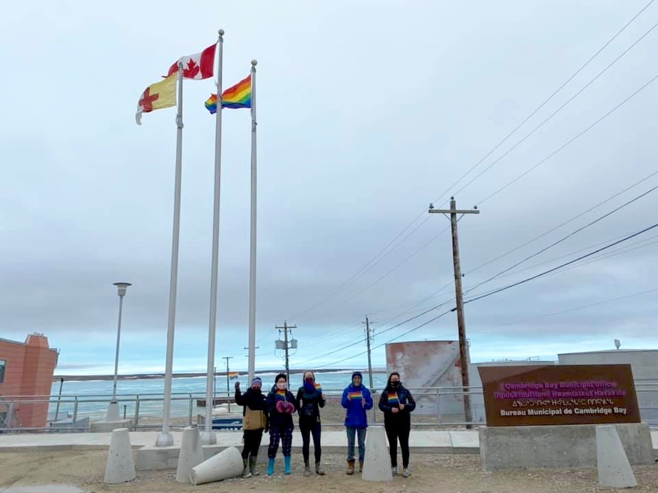 """Cambridge Bay raised a Pride flag for the first time on Thursday. Mayor Pamela Gross said she hopes this makes people feel like they can be their """"true authentic selves."""" In a Facebook post, she said, """"If you're wanting to come out and need an outlet, please know that there are people who can help and are there to talk when your time is right."""" From left: Adele Ohokak, Onnalyssia Ohokak, Beth Sampson, Sinclair Lyall and Cambridge Bay Mayor Pamela Gross. (Photo by Tommy Evetalegak, Municipality of Cambridge Bay)"""