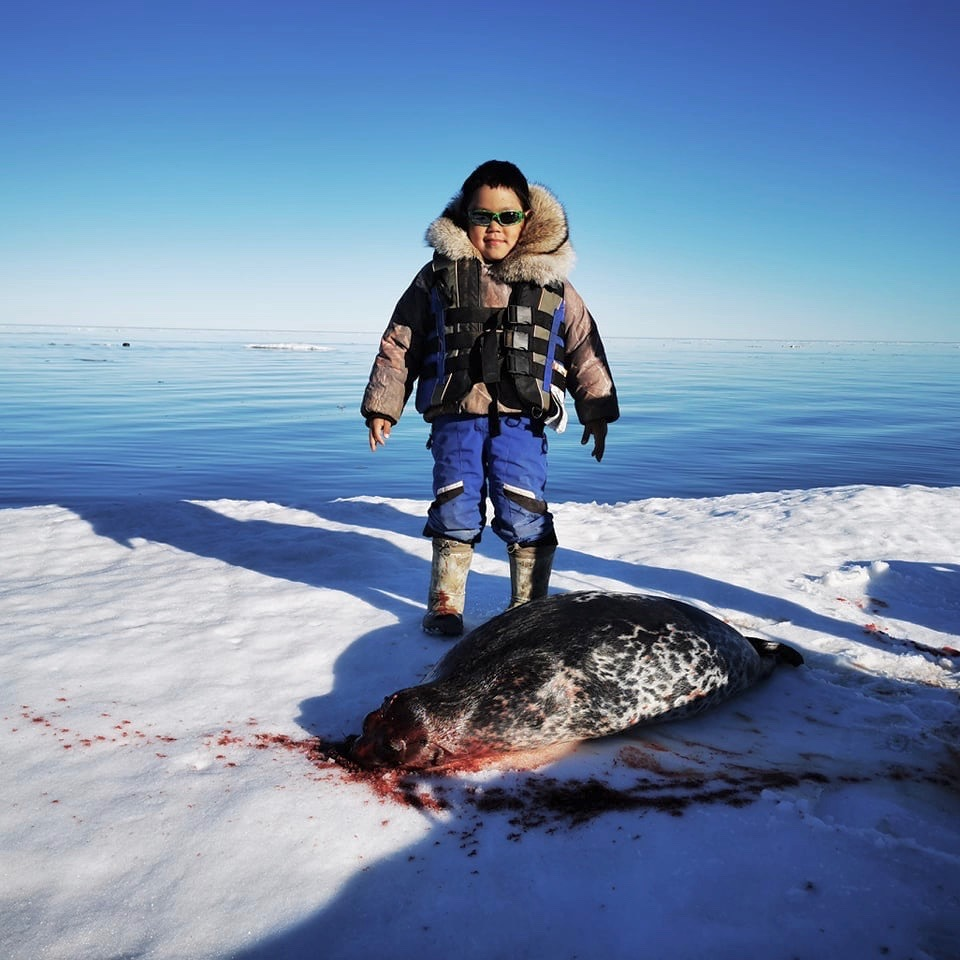 """Arviat's six-year-old Brody Panigoniak is seen after hunting his first seal on Tuesday evening. After catching the animal, a bright smile spread across his face, said his mother, Hilda Panigoniak. """"My son was so happy."""" She said he asked to go boating for the first time, so she, her boyfriend and her sister got ready and set off on the water after work. To celebrate Brody's catch, they held a game for the community and gave out some change, goodies, and one lucky winner got $100 cash. (Photo courtesy of Hilda Panigoniak)"""